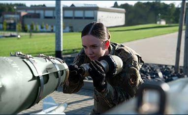 Female ammo tech inserting a DSU-33 Proximity Sensor into the back of a munition. A grey government building is behind her.