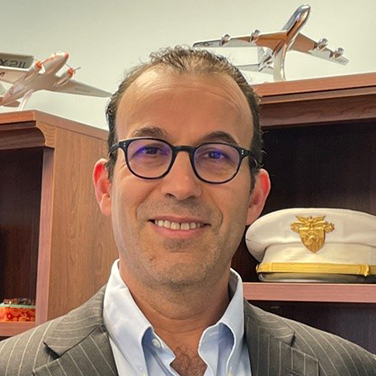 Image of Moshe Schwartz. Schwartz stands in front of a bookshelf with a military hat and model airplanes. He wears a light suit with a blue shirt and dark, rounded glasses. He smiles with his teeth showing.