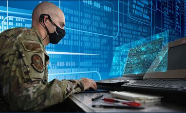 24th Annual Systems and Mission Engineering Conference - Image of a man in military attire sitting at a computer; he is wearing a face mask.