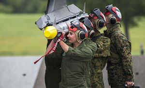 Image of four military personnel carrying a missile. They have on camos and wear a helmet with goggles.